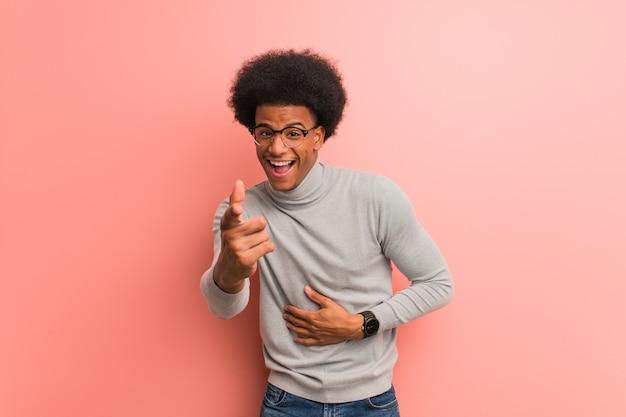 De jonge afrikaanse amerikaanse mens over een roze muur droomt van het bereiken van doelen en doeleinden