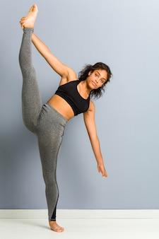 De jonge afrikaanse amerikaanse sportieve vrouw die ritmische gymnastiek doet stelt