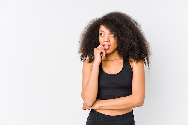 De jonge afrikaanse amerikaanse sportieve vrouw ontspande het denken over iets bekijkend een exemplaarruimte.