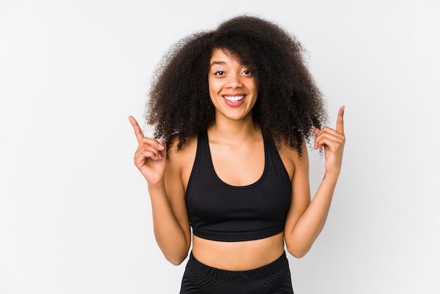 De jonge afrikaanse amerikaanse sportieve vrouw wijst op met beide voorvingers die omhoog een lege ruimte tonen.