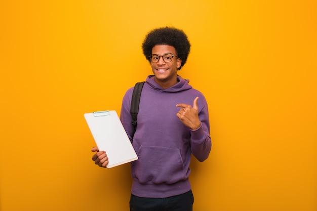 De jonge afrikaanse amerikaanse studentenmens die een klembord verrast houdt, voelt succesvol en welvarend