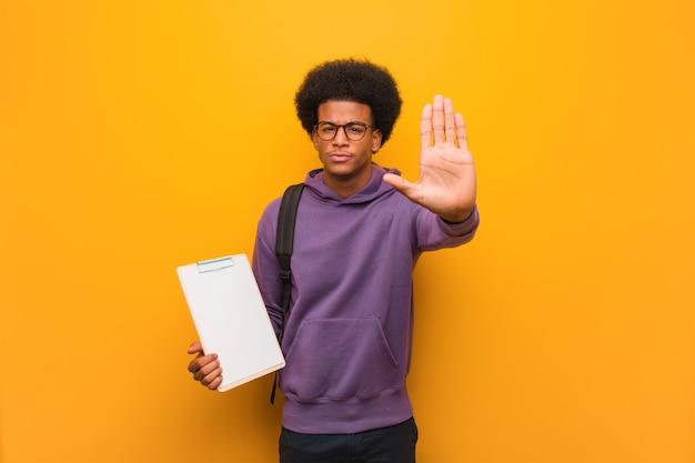 De jonge afrikaanse amerikaanse studentenmens die klembord houden het zetten dient voorzijde in