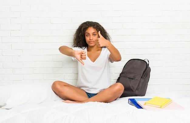 De jonge afrikaanse amerikaanse studentenvrouw op het bed die duimen tonen en duimen neer, moeilijk kiest
