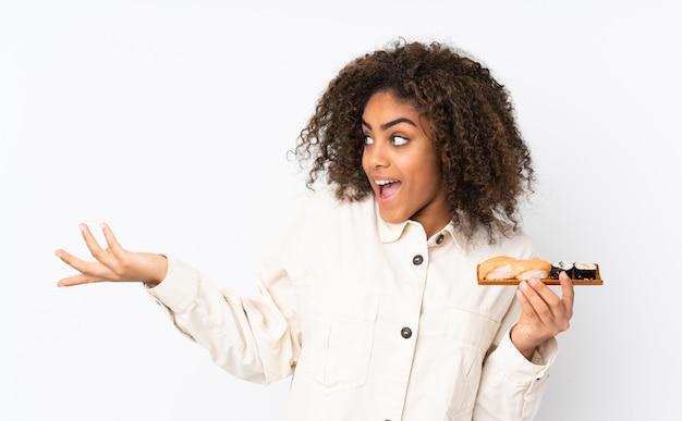 De jonge afrikaanse amerikaanse sushi van de vrouwenholding op witte muur met verraste gelaatsuitdrukking