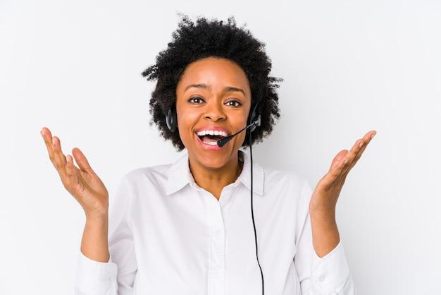 De jonge afrikaanse amerikaanse telemarketervrouw isoleerde het ontvangen van een prettige verrassing, opgewekte en opheffende handen.