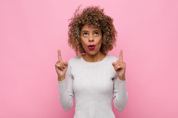De jonge afrikaanse amerikaanse vrouw die awed voelt en met open mond omhoog wijzend met een geschokte en verraste blik tegen roze muur