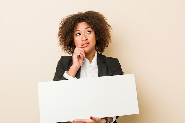 De jonge afrikaanse amerikaanse vrouw die een aanplakbiljet houdt ontspande het denken over iets