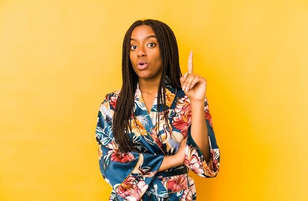 De jonge afrikaanse amerikaanse vrouw die een aziatische pijama draagt isoleerde het hebben van één of ander groot idee, concept creativiteit.