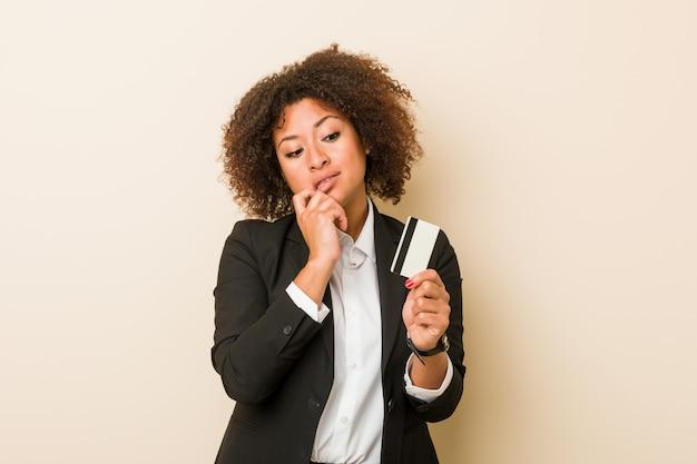 De jonge afrikaanse amerikaanse vrouw die een creditcard houden ontspande het denken over iets bekijkend een exemplaarruimte.