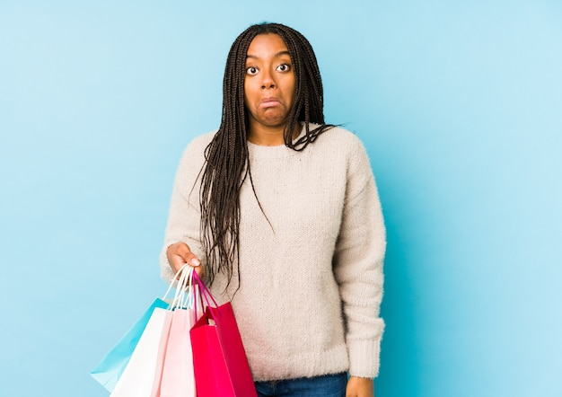De jonge afrikaanse amerikaanse vrouw die een geïsoleerde boodschappentas houdt, haalt schouders op en opent verwarde ogen.