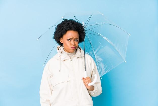 De jonge afrikaanse amerikaanse vrouw die een paraplu houdt geïsoleerd verward, voelt twijfelachtig en onzeker.