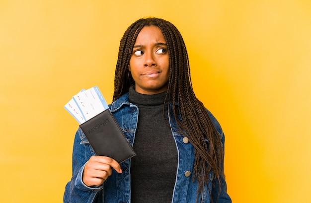 De jonge afrikaanse amerikaanse vrouw die een paspoort geïsoleerd verward houdt, voelt twijfelachtig en onzeker.