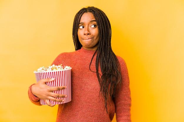 De jonge afrikaanse amerikaanse vrouw die een popcorn houdt isoleert verward, voelt twijfelachtig en onzeker.