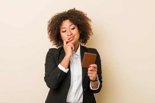 De jonge afrikaanse amerikaanse vrouw die een portefeuille houden ontspande het denken over iets bekijkend een exemplaarruimte.