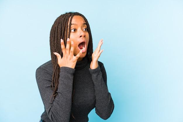 De jonge afrikaanse amerikaanse vrouw die op blauwe achtergrond wordt geïsoleerd schreeuwt luid, houdt ogen geopend en handen gespannen.
