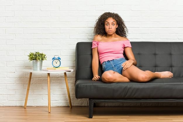De jonge afrikaanse amerikaanse vrouwenzitting op de bank haalt schouders op en verwarde open ogen.