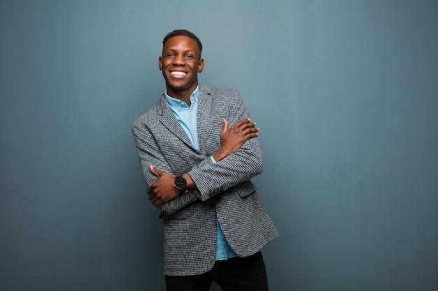 De jonge afrikaanse amerikaanse zwarte mens die gelukkig met gekruiste wapens lachen, met een ontspannen, positieve en tevreden stelt over grungemuur