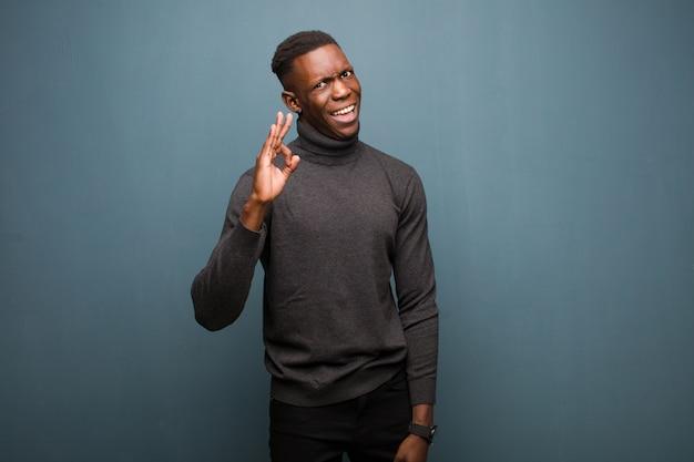 De jonge afrikaanse amerikaanse zwarte mens die succesvol en tevreden voelen, glimlachend met wijd open mond, die ok teken maken met overhandigt grungemuur