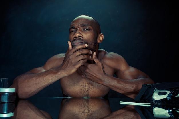 De jonge afrikaanse man in de slaapkamer zit voor de spiegel na zijn baard thuis te krabben