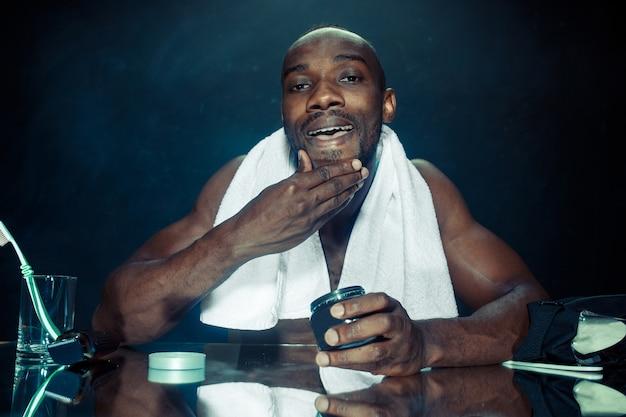 De jonge afrikaanse man in slaapkamer zit voor de spiegel na zijn baard thuis te krabben. menselijke emoties concept. after shave cream concepten