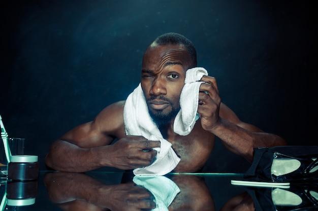 De jonge afrikaanse man in slaapkamer zit voor de spiegel na zijn baard thuis te krabben. menselijke emoties concept