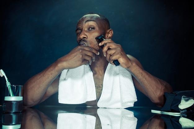 De jonge afrikaanse man in slaapkamer zit voor de spiegel zijn baard thuis krabben. menselijke emoties concept