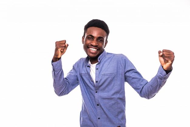 De jonge afrikaanse mens met opgeheven handen viert overwinning die op witte muur wordt geïsoleerd