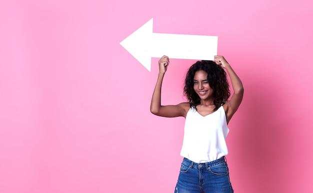 De jonge afrikaanse pijl die van de vrouwenholding op exemplaarruimte richt die over roze bannerruimte wordt geïsoleerd.
