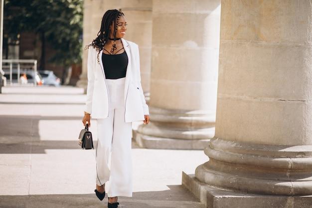 De jonge afrikaanse vrouw kleedde zich in wit kostuum buiten de straat