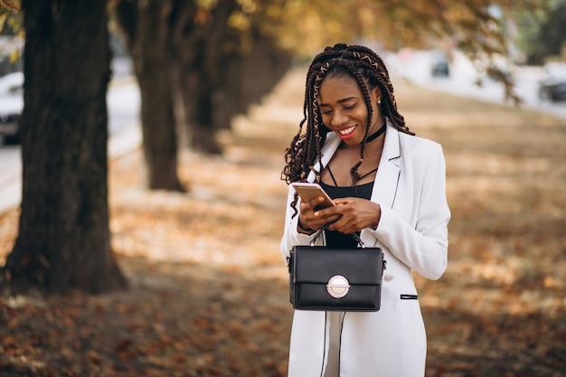 De jonge afrikaanse vrouw kleedde zich in wit kostuum in park