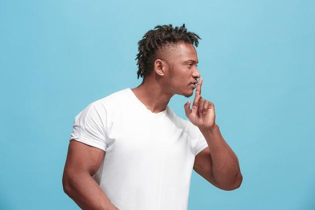 De jonge afro-amerikaanse man fluistert een geheim achter haar hand over blauw