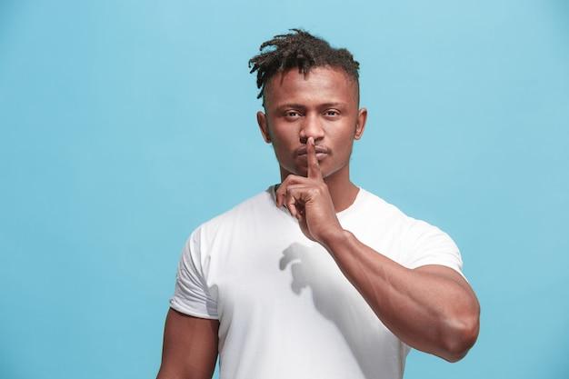 De jonge afro-amerikaanse man fluistert een geheim achter haar hand over de blauwe muur