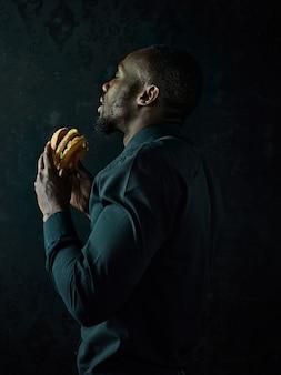 De jonge afro-amerikaanse man hamburger eten en wegkijken op zwarte studio