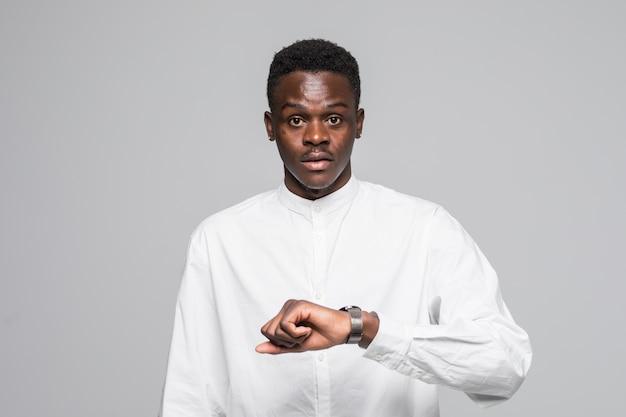 De jonge afro amerikaanse mens in overhemd kijkt dichtbij horloge dat op grijze achtergrond wordt geïsoleerd