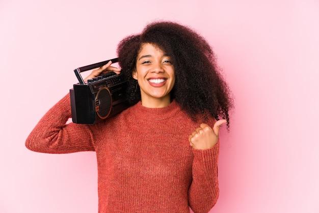 De jonge afrovrouw die een cassete houden isoleerde omhoog glimlachend en duim opheffend