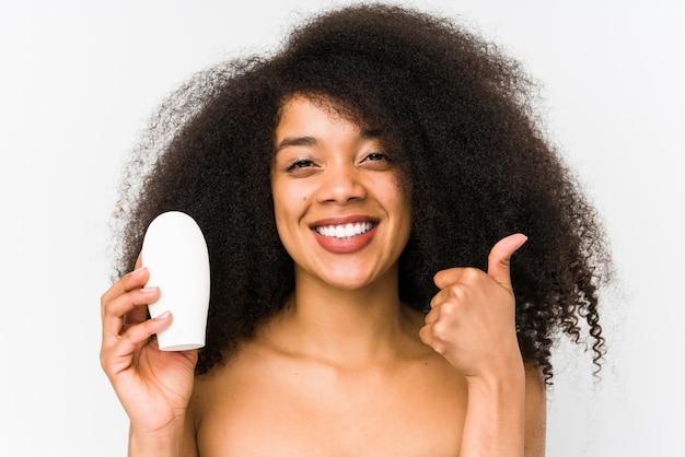De jonge afrovrouw die een vochtinbrengende crème houden isoleerde omhoog het glimlachen en het opheffen van duim
