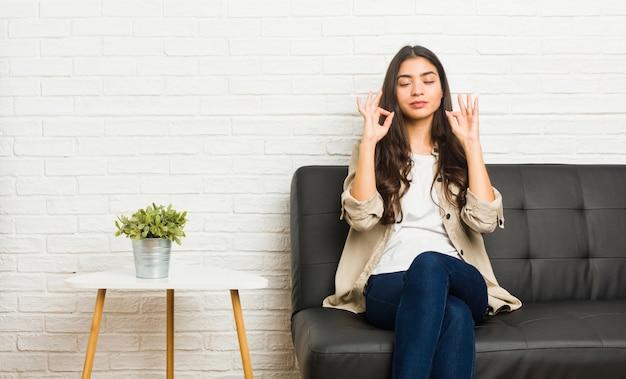 De jonge arabische bank van de vrouwenzitting ontspant na harde werkdag, voert zij yoga uit.