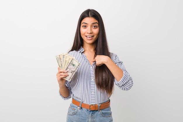 De jonge arabische dollars van de vrouwenholding verrast wijzend op zich, breed glimlachend.