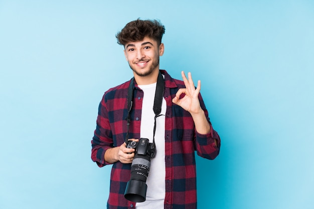 De jonge arabische fotograafmens isoleerde vrolijk en zeker tonend ok gebaar.