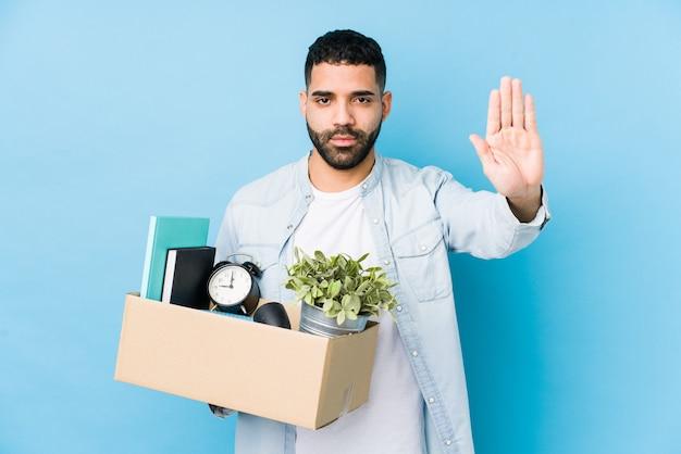 De jonge arabische mens die zich naar een nieuw huis bewegen isoleerde status met uitgestrekte hand die eindeteken tonen, die u verhinderen.