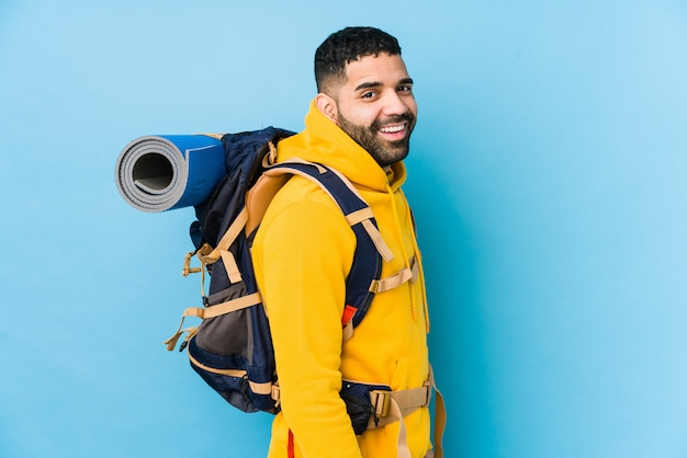 De jonge arabische reizigers backpacker mens kijkt opzij glimlachend, vrolijk en aangenaam.