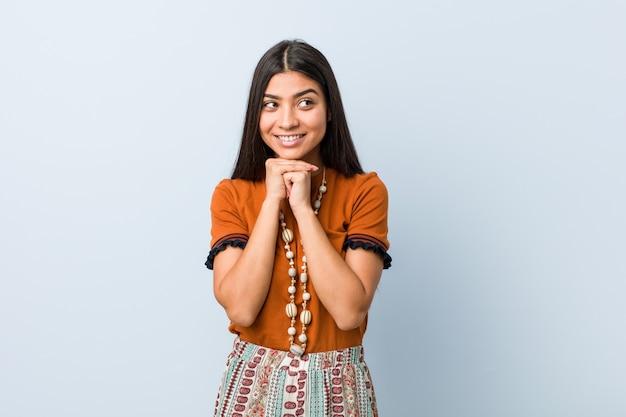 De jonge arabische vrouw houdt handen onder kin, kijkt gelukkig opzij.