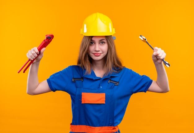 De jonge arbeider van de vrouwenbouwer in eenvormige bouw en de moersleutels van de veiligheidshelmholding in opgeheven handen die zich zelfverzekerd over oranje muur bevinden kijken