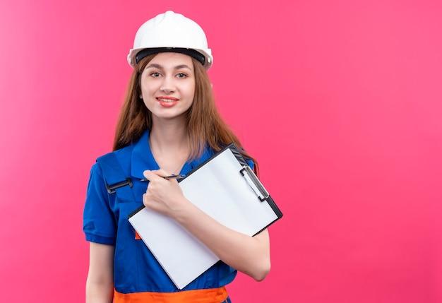 De jonge arbeider van de vrouwenbouwer in eenvormige bouw en het klembord die van de veiligheidshelmholding zelfverzekerd over roze muur kijken