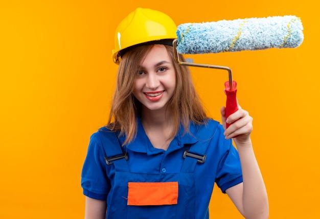 De jonge arbeider van de vrouwenbouwer in eenvormige bouw en veiligheidshelm die de verfroller glimlachend zelfverzekerd over oranje muur houden