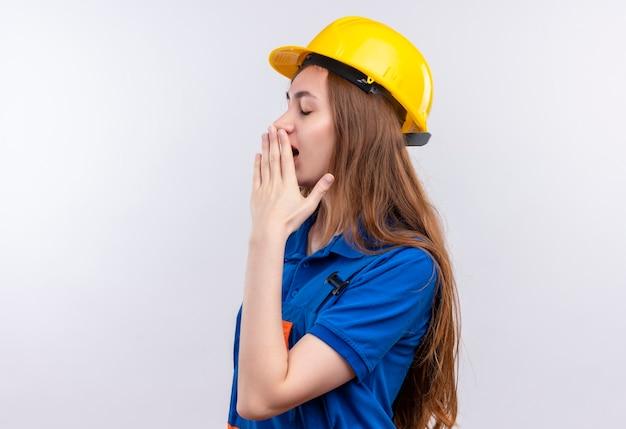 De jonge arbeider van de vrouwenbouwer in eenvormige bouw en veiligheidshelm die die mond behandelen met hand die moe status over witte muur kijken