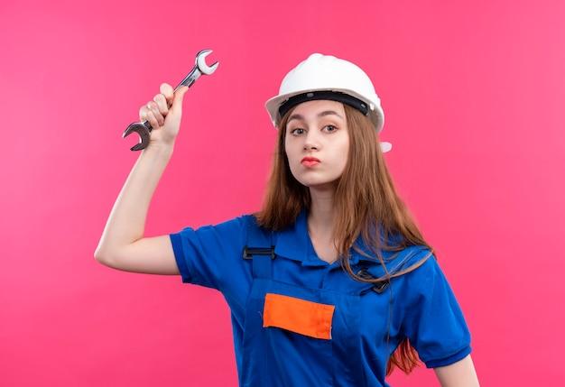 De jonge arbeider van de vrouwenbouwer in eenvormige bouw en veiligheidshelm die een moersleutel met ernstig gezicht slingeren dat zich over roze muur bevindt