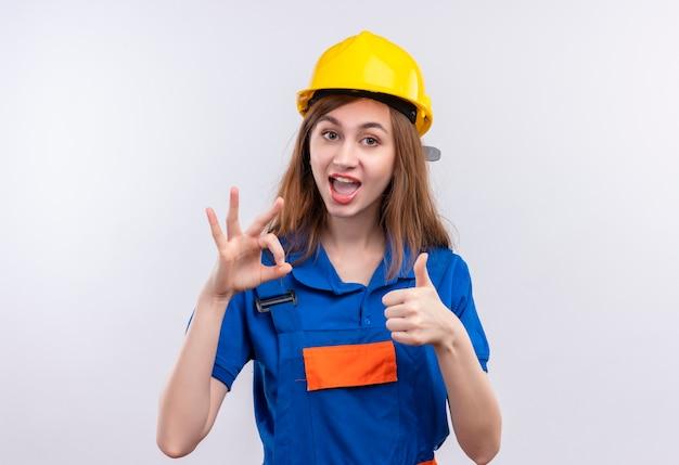 De jonge arbeider van de vrouwenbouwer in eenvormige bouw en veiligheidshelm die in grote lijnen duimen tonen die omhoog en ok teken zich over witte muur bevinden