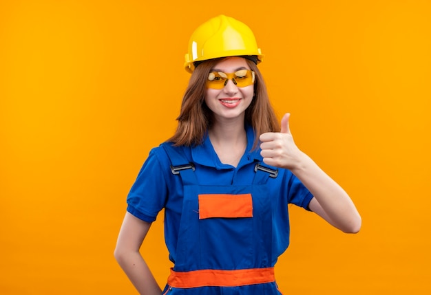 De jonge arbeider van de vrouwenbouwer in eenvormige bouw en veiligheidshelm die in grote lijnen glimlachen tonen die omhoog zich over oranje muur bevinden