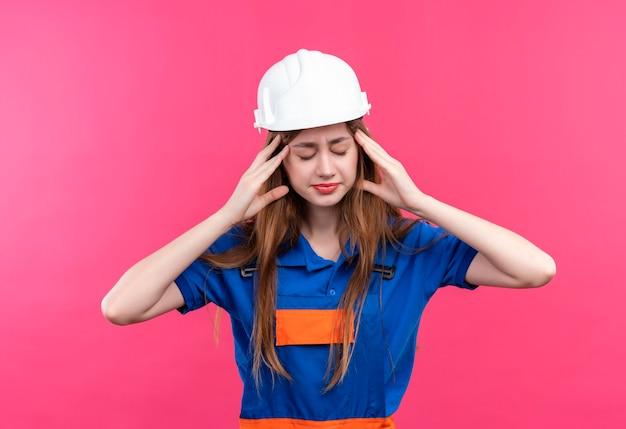 De jonge arbeider van de vrouwenbouwer in eenvormige bouw en veiligheidshelm die moe en overwerkt met hoofdpijn kijken die zich over roze muur bevindt